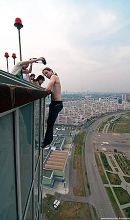 Человек без страховки висит на карнизе крыши. Высота под ним - порядка 120 метров.