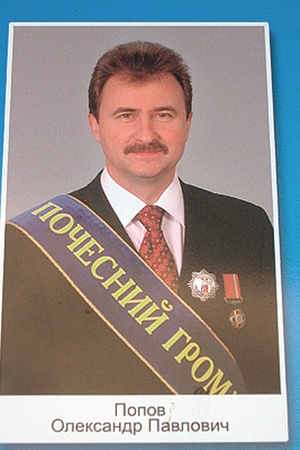 Попов улыбается горожанам с доски почета.