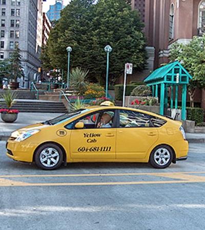 Toyota Prius с гибридным двигателем работает в качестве такси на улицах Ванкувера в Канаде.