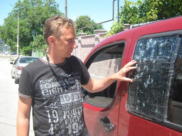 Андрей показывает поврежедния на авто.