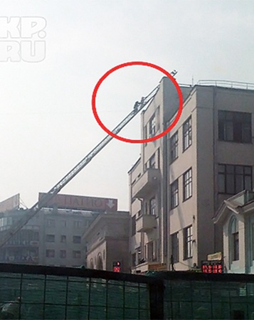 Пожарный снимает девушку с крыши.