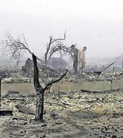 Деревня Передельцы Рязанской области. Люди стоят на фундаменте дома - все, что от него осталось после страшного пожара. Все вокруг усыпано опаленными яблоками...