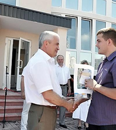 Молодежь получает ключи от нового жилья из рук мэра.