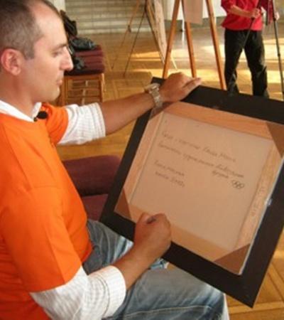 На обратной стороне полотна чемпион оставил свою подпись и нарисовал олимпийские кольца.