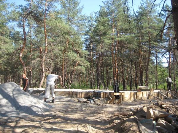В сосновом лесу возле Кировского рабочие заканчивают делать фундамент для двух коттеджей.
