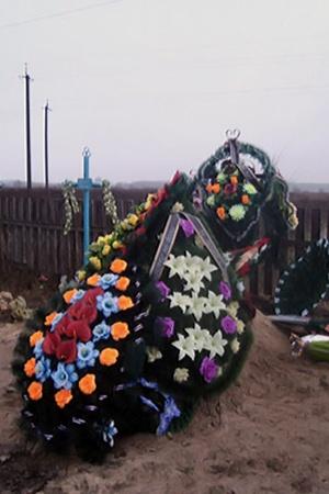На могиле повесившегося учителя много цветов от коллег и детей.