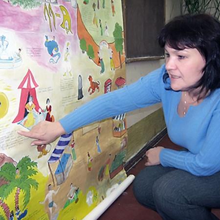 Классный руководитель девушки Елена Сильченко показывает стенгазету, сделанную к выпускному вечеру, в 2004 году.