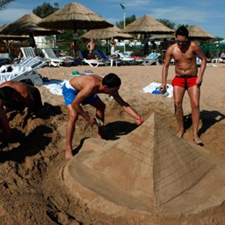 Те, у кого не хватает духу зайти в воду, копаются в песочке.