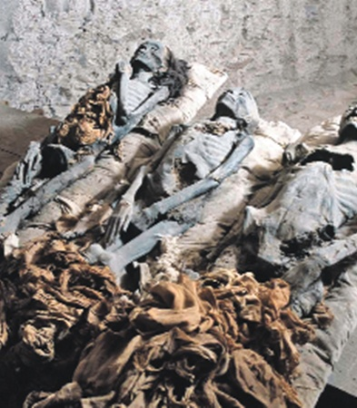 Мумии, обнаруженные в 1898 году: крайняя слева - «старшая», крайняя справа - «младшая»,  между ними - неустановленный юноша. Одна из двух женских мумий, возможно, и есть Нефертити.