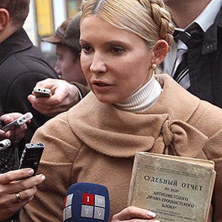 Намекая на репрессии, Леди Ю ходит на допросы с судебным отчетом по делу антисоветского правотроцкистского блока.