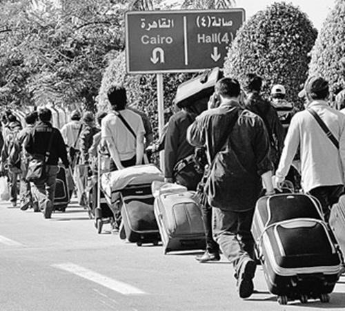 Многие туристы с багажом вереницами тянутся в аэропорт, чтобы улететь из неспокойной страны. Фото АП.