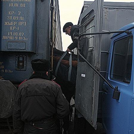 Зэков перегружают из автозака в вагон под охраной конвойных с собаками.