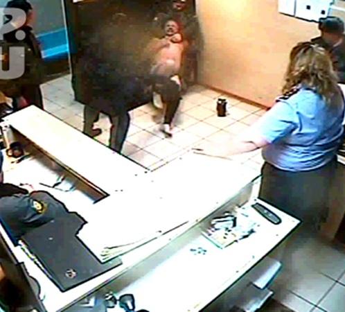 ...насильно стягивает одежду, пока второй сотрудник держит мужчину за шею...