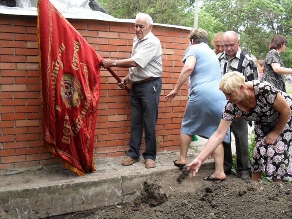 Родственники бросают землю в могилу.