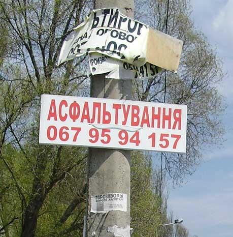 Как издевка над всеми здешними прохожими и проезжающими - табличка с рекламой… асфальтоукладчиков! Фото Игоря ВОРОБЬЕВА.