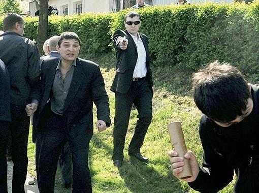 Избитый Святослав Сопильнык направляет пистолет вниз, чтоб не попасть в людей. Фото АП.