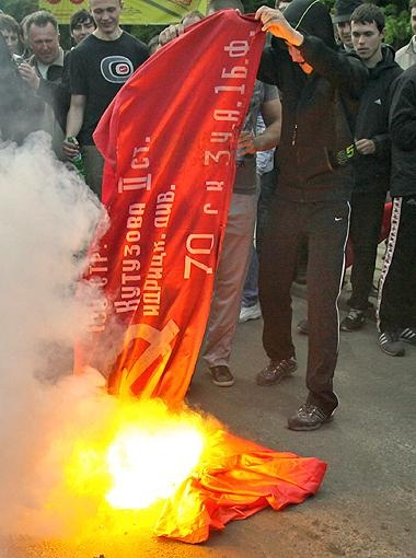 Молодые активисты правых организаций жгут Знамя Победы. Фото АП.