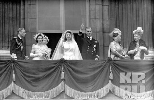 Королева Елизавета Вторая с супругом Герцогом Эдинбургским машут толпе с балкона Букингемского дворца 20 ноября 1947 года. Слева направо: король Георг VI, принцесса Маргарет, леди Мария Кэмбридж, невеста с женихом, королева Елизавета и королева Мария Фото: АП
