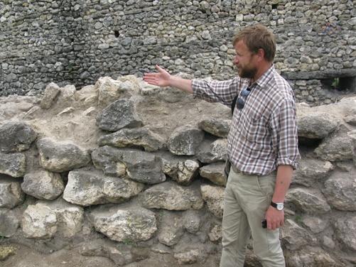 Директор заповедника Юрий Зайцев указывает на возводимую каменную стену.