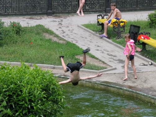Пока государевы мужи благоустраивают город, детвора спасается от жары в городских прудах.