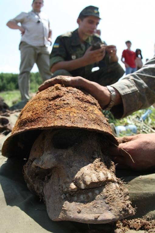 При попытке снять небольшой слой земли археологи обнаружили металлическую каску, под которой виднелся череп