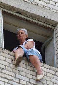 Женщина поднялась на 10-й этаж и вылезла в оконный проем над лестничной площадкой. Фото Алексея Кравцова.