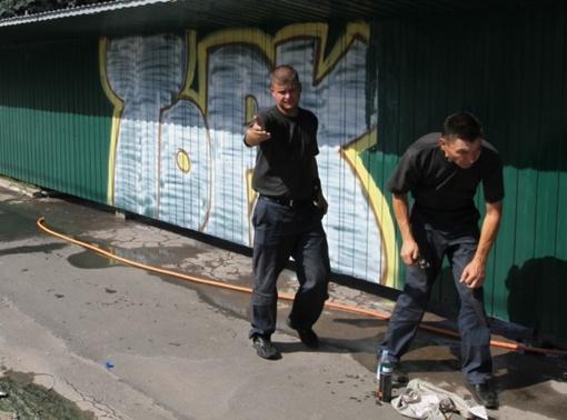 Два молодых человека в униформе активно протестовали против съемки художественной надписи. Фото: 62.