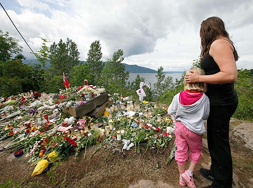 Остров Утойя, где погибло 68 человек, усыпан цветами и поминальными свечами.