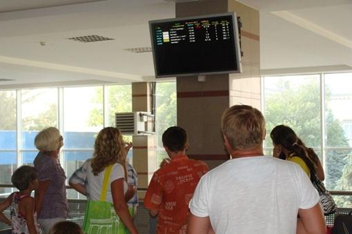 На табло люди ждут информацию о прибытии долгожданного самолета