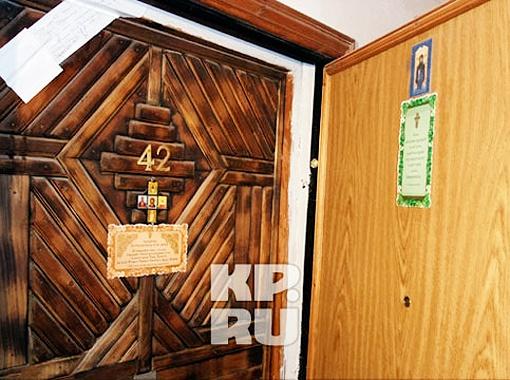 На двери наклеены иконки и листки с текстами молитв. Фото Игоря Корнеева.