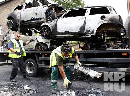 Ночью вандалы поджигают припаркованные автомобили, утром остается лишь убирать обгоревшие железные кузова. Фото: REUTERS