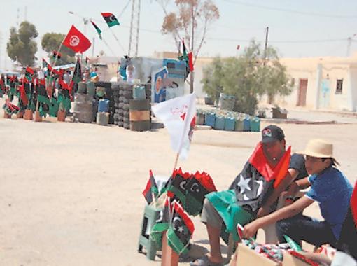 Самый ходовой товар в Тунисе по мере приближения к ливийской границе - повстанческие флаги и бензин в канистрах.