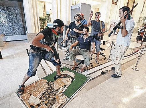Повстанцы ворвались в резиденцию Каддафи и с удовольствием позируют на фоне лика