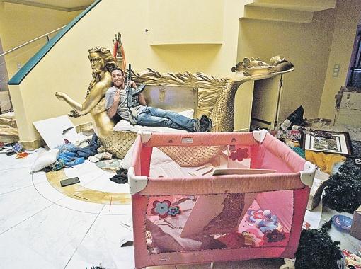 Какое символичное фото! Повстанец разлегся на диванчике в виде золоченой русалки с лицом Аиши Каддафи - дочери полковника. Как тут не вспомнить, что операция по захвату Триполи как раз носила кодовое название