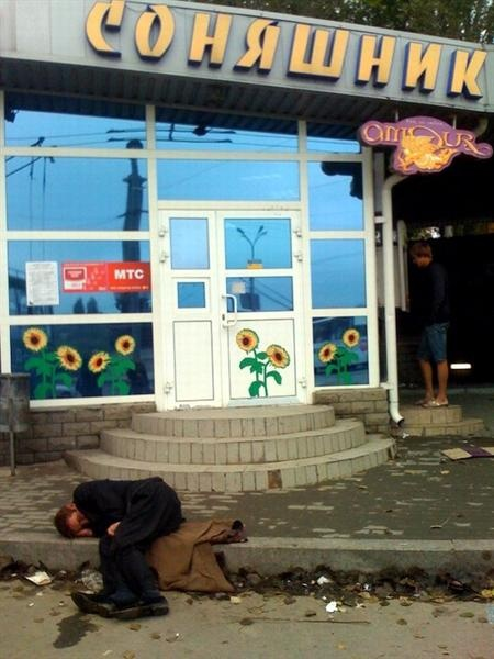 Мужчина спит субботним утром под магазином на площади Конституции в Донецке.