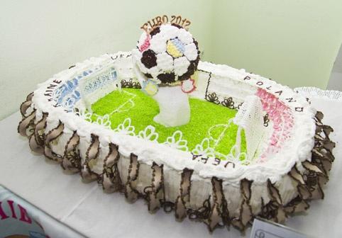 Для изготовления ее бисквитного торта в виде стадиона с символикой