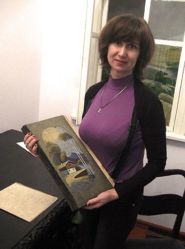 Директор музея показывает альбом Драгомановых, который уцелел во время войны.