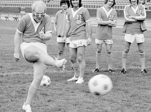 Смотрите, как может! Элтон Джон показывает легендарному Джорджу Бесту (третий слева), как надо бить по мячу. Фото с сайта thevintagefootballclub.blogspot.com