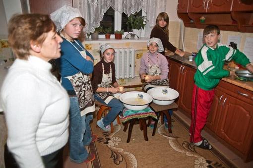 В семейных группах интерната дети под присмотром педагога учатся вместе готовить ужин.