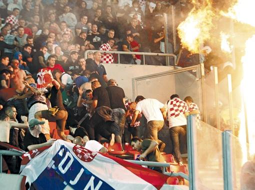 Болельщики сборной Хорватии во время отборочного матча чемпионата Европы спасаются бегством от греческих фанатов, которые подожгли их сектор.