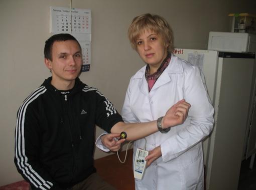 Нейрохирург Людмила Дунаевская показывает, как легко, несколькими нажатиями кнопок на пульте управления, можно заставить двигаться кисть руки.