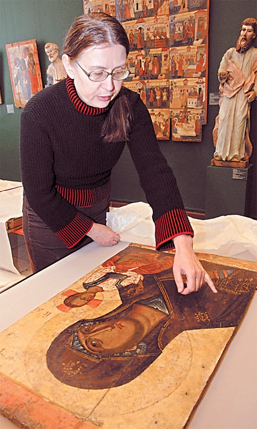 Галина Беликова показывает, как на иконе XIV века вздулась краска.