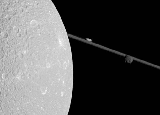Диона закрывает правую часть изображения. Слева, на фоне колец, ближе к Дионе находится Прометей, а слева от него - Эпиметей. Фото NASA