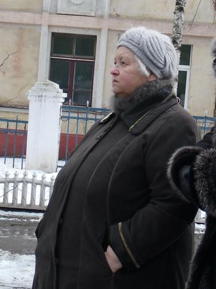 Нина Радченко с болью смотрит, как из окна квартиры выбрасывают ее сгоревшее добро.