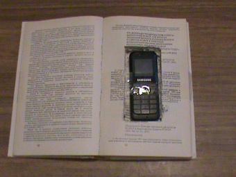 Мобильный в книге. Фото из архива