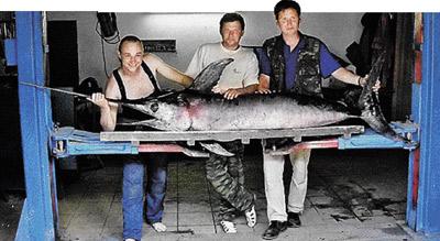 Чтобы вытащить рыбину, Алексею Лятуну (на фото слева) понадобилась помощь друзей.