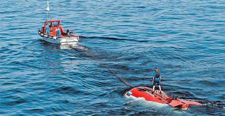«Мир» с гидронавтами внутри краном спускают на воду и катером буксируют подальше от баржи.