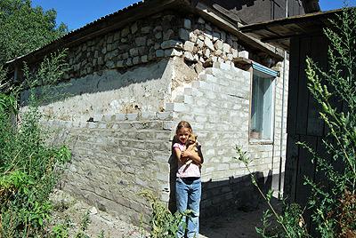6-летняя Аня Мельникова возле своего дома в Авиловке (год назад взрывом вынесло стенку жилища).
