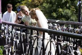 Молодожены вешают на перилах моста замочки в знак вечной любви.