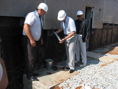 - Торжественный момент презентации - закладка капсулы в честь начала строительства нового жилого дома.